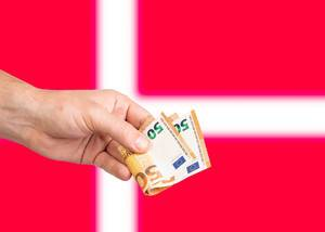 Hand with Euro banknotes over flag of Denmark