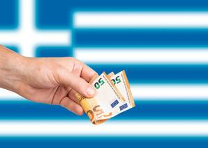 Hand with Euro banknotes over flag of Greece