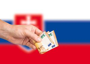 Hand with Euro banknotes over flag of Slovakia