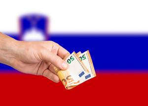 Hand with Euro banknotes over flag of Slovenia