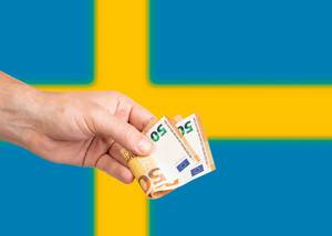 Hand with Euro banknotes over flag of Sweden