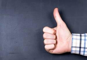 Hand zeigt Daumen hoch vor schwarzer Wand, zeigt Zustimmung