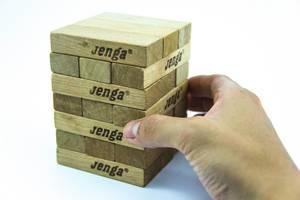 Hand zeigt einen Spielblock aus einem Jenga-Turm