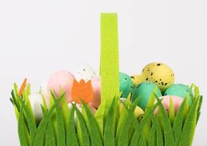 Handbemalte Ostereier in grünem, mit Gras und Tulpen verziertem Osterkorb vor weißem Hintergrund