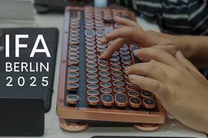 """Hände tippen auf einer besonderen Computertastatur im Retrolook, neben dem Bildtitel """"IFA Berlin 2025"""""""