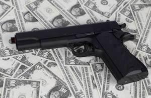 Handfeuerwaffe auf Hintergrund aus Banknoten