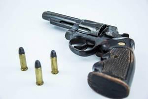Handfeuerwaffe mit Munition auf weißem Hintergrund