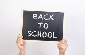 Hands holding blackboard with text Back to school
