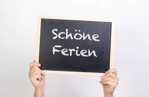 Hands holding blackboard with text Schöne Ferien