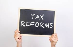 Hands holding blackboard with text Tax reform