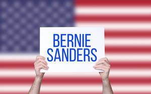 Hands holding board with Bernie Sanders text with USA flag background