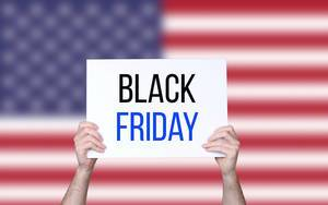 Hands holding board with Black Friday text with USA flag background