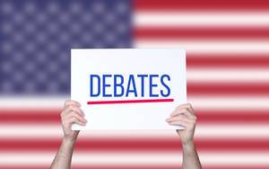 Hands holding board with Debates text with USA flag background