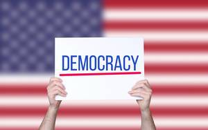 Hands holding board with Democracy text with USA flag background