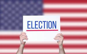 Hands holding board with Election text with USA flag background.jpg
