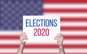 Hands holding board with Elections 2020 text with USA flag background.jpg