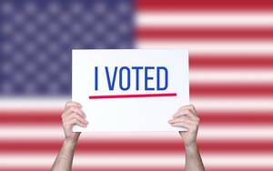 Hands holding board with I Voted text with USA flag background