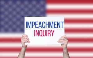 Hands holding board with Impeachment Inquiry text with USA flag background