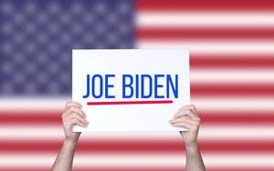 Hands holding board with Joe Biden text with USA flag background