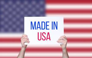 Hands holding board with Made in USA text with USA flag background