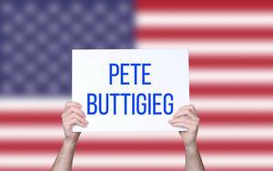 Hands holding board with Pete Buttigieg text with USA flag background
