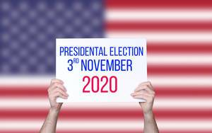 Hands holding board with Presidental Election 2020 date with USA flag background