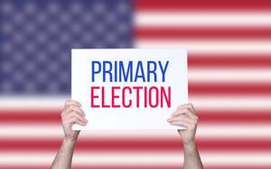 Hands holding board with Primary Election text with USA flag background