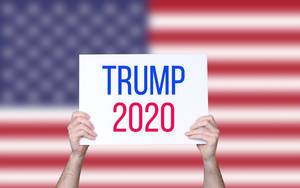 Hands holding board with Trump 2020 text with USA flag background