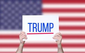 Hands holding board with Trump text with USA flag background.jpg