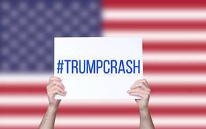 Hands holding board with #TrumpCrash text with USA flag background.jpg