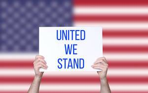 Hands holding board with United we stand text with USA flag background