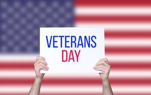 Hands holding board with Veterans Day text with USA flag background