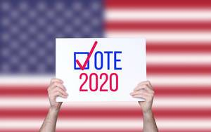 Hands holding board with Vote 2020 concept with USA flag background
