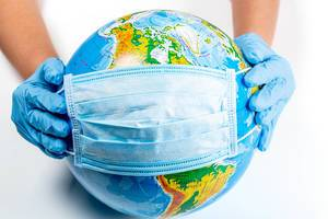 Hands in gloves hold a globe in a medical mask. The concept of the fight against coronavirus in the world