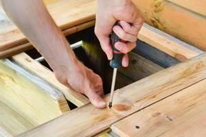 Handwerker dreht eine Schraube mit einem Schraubenzieher ein