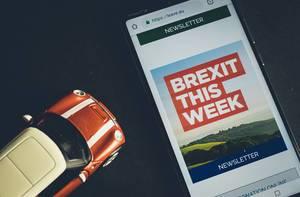 """Handy zeigt """"Brexit This Week"""" - Newsletter der leave.eu Website, neben britischem Spielzeug-Auto"""