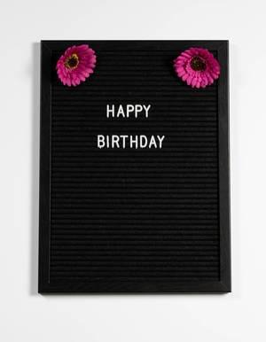 Happy birthday auf einem schwarzen Brett mit Blumen