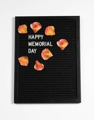 Happy memorial day auf einem schwarzen Brett mit Blumenblättern