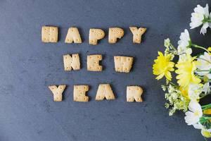 Happy new year aus Buchstabenkeksen vor schwarzem Hintergrund geschrieben