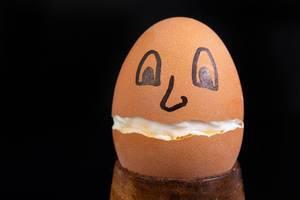 Hartgekochtes, in der Mitte gebrochenes Ei mit aufgemaltem Gesicht vor schwarzem Hintergrund