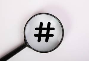 Hashtagsymbol und Rautezeichen in schwarz auf weiß, vergrößert dargestellt unter einer Lupe