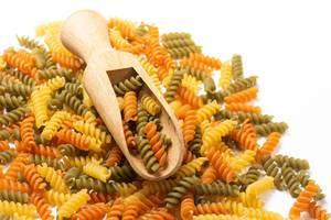 Haufen dreifarbige, ungekochte Fusilli Pasta mit Holzschaufel vor weißem Hintergrund