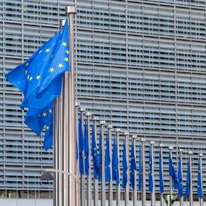 Hauptsitz der Europäischen Kommission in Brüssel mit Flaggen der Europäischen Union im Vordergrund