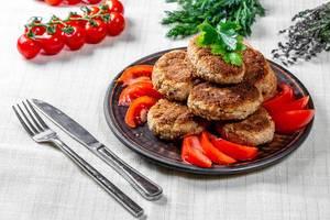 Hausgemachte Fleischbuletten neben Tomaten, Kräutern und Besteck