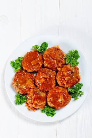 Hausgemachte Frikadellen mit Tomatensoße auf einem Teller mit Petersilie - AUfischt