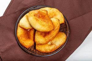 Hausgemachte frittierte und luftige Teigtaschen auf einem dunklen Teller und braunem Tuch als Hintergrund