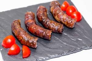 Hausgemachte, gebratene Wurst mit geschnittenen Tomaten auf schwarzer Platte