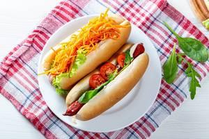 Hausgemachte Hotdogs mit frischen Zutaten, auf einem Geschirrtuch auf dem Küchentisch