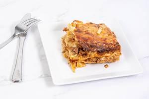 Hausgemachte Lasagne auf einem quadratischen Teller, mit Besteck, auf einer Marmoroberfläche