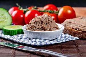 Hausgemachte Leberpastete mit Gemüse und dunklem Brot auf einem gedeckten Tisch